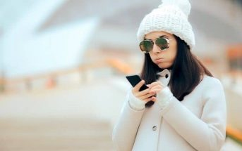 woman looking at phone wondering why she is still single