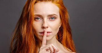 woman with finger over her lips to illustrate talking less