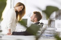man and woman having an affair in an office