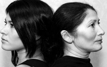black and white image of a mother and daughter standing back to back