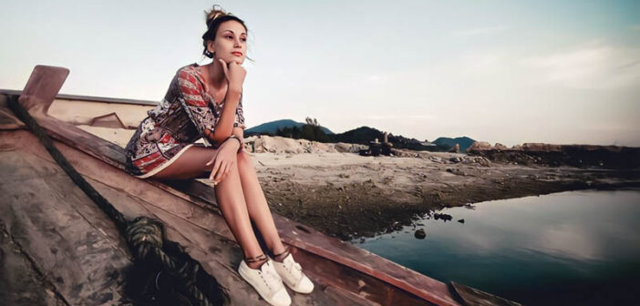 young woman sitting on shipwrecked boat feeling stuck in her life