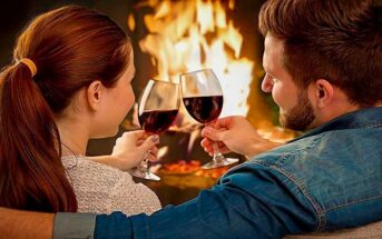 a couple with wine in front of a fire enjoying a date night at home