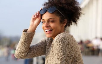 young woman smiling with sun on her face - concept of improving your life