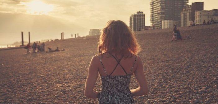 woman walking alone on beach at sunset