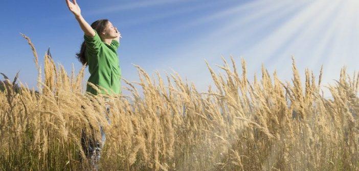 woman with arms in the air facing toward sun - illustrating spiritual goals