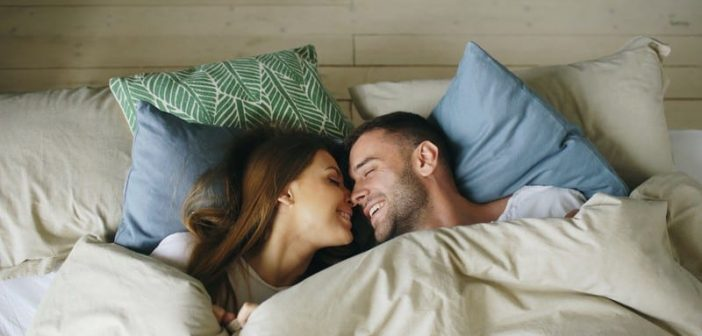 happy man and woman in bed - illustrating what a man wants in a woman