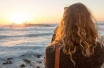 woman looking at sunrise over the ocean illustrating hope