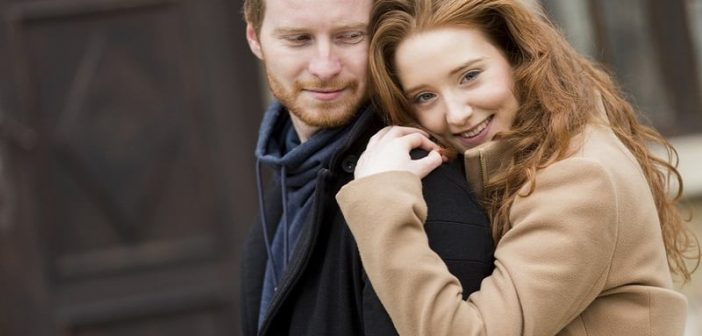 woman embracing man from behind to illustrate showing appreciation