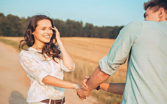 happy young woman pulling on hand of boyfriend in a field - illustrating complimenting a guy