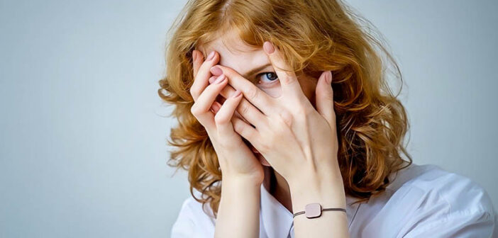 red-haired woman with eyes peeping through fingers illustrating a fear of being judged