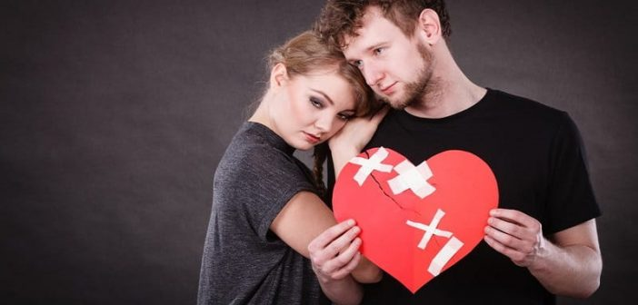 couple holding a patched up red heart