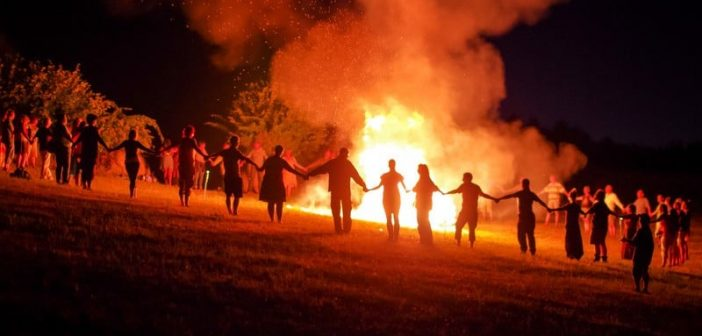 many people holding hands around a large bonfire