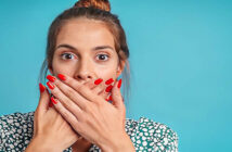 woman covering her mouth with her hands to stop lying
