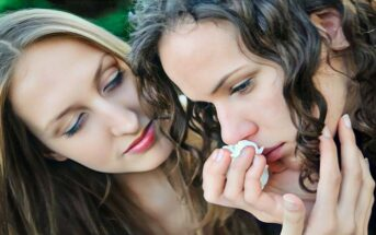 woman comforting sad friend who is holding a tissue to her nose