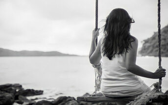 black and white photo of a young woman sitting on a swing looking out to sea - illustrating not knowing who you are