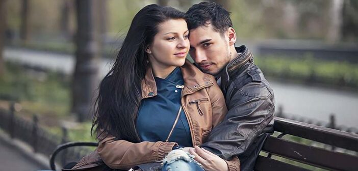 a young couple sitting on a park bench