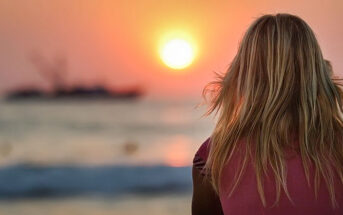 young woman facing sunset - illustrating finding inner peace
