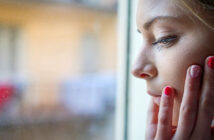 young woman looking out of window and worrying about the future