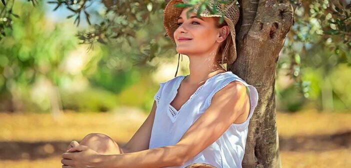 peaceful looking woman sitting under a tree - illustrating not letting things bother you