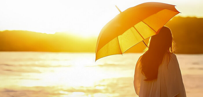 woman with sun umbrella looking at sun illustrating the aspects of life
