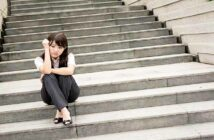 anxious young businesswoman sitting on some steps illustrating a fear of success