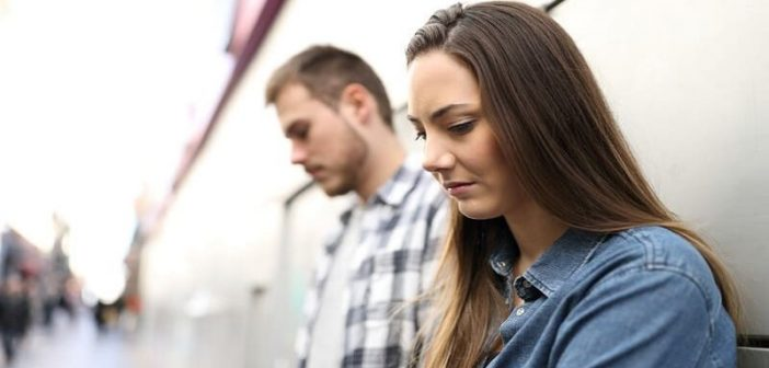 couple leaning against wall thinking the other is too good for them