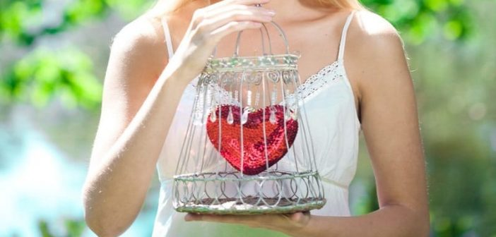 woman holding her heart in a cage illustrating needing to open up to love