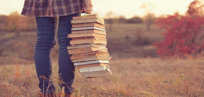 woman with stack of books in nature - illustrating hobbies for introverts