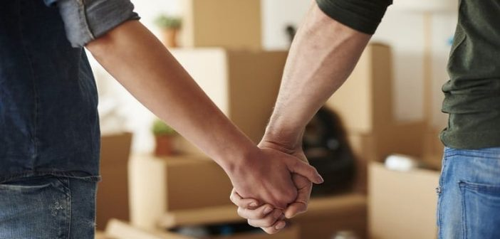 a couple holding hands after moving in together with cardboard boxes in the background