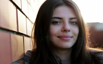 young woman smiling toward camera illustrating being a nice person