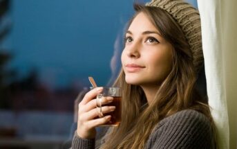 smiling thoughtful woman holding a hot drink - illustrating being the best version of yourself