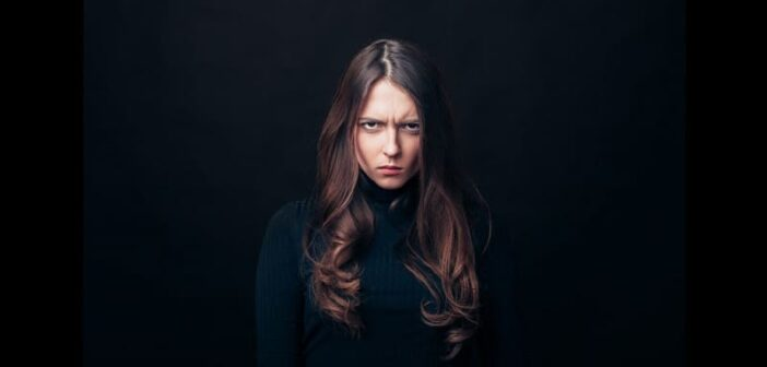 angry looking woman on black background