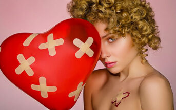 woman holding heart balloon with plasters all over it illustrating the pain and hurt of love