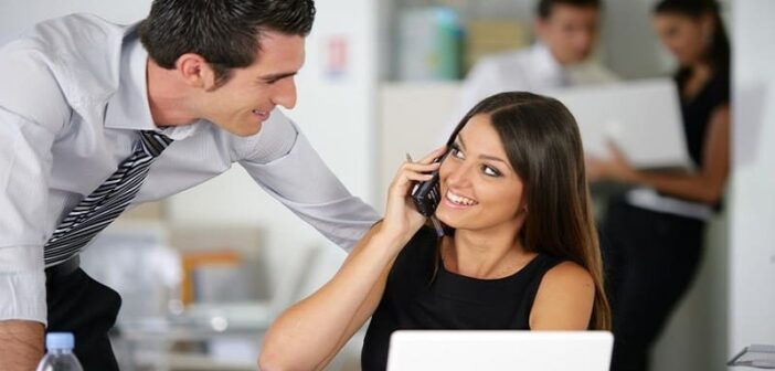man leaning toward female coworker showing that he likes her