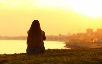 silhouette of a woman looking out across a coastal city - illustrating taking a break from life