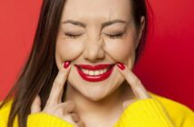 woman pushing sides of her mouth up to form a smile - illustrating toxic positivity