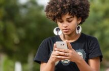young African American woman texting a guy to ask him out on a date