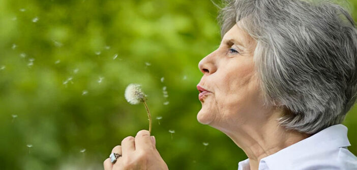 old woman blowing dandelion seeds - illustrating leaving a legacy