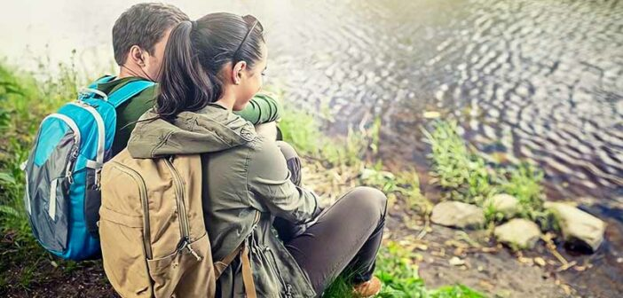 couple spending quality time together sitting by a stream