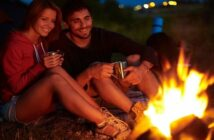 couple having romantic time around a campfire