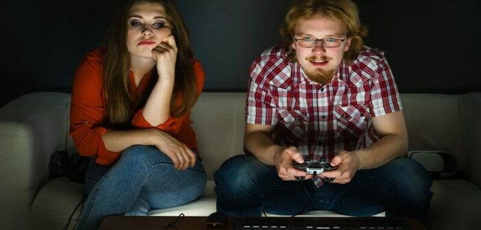 emotionally immature man playing video games and ignoring his girlfriend