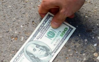 person finding a one hundred dollar bill on the ground - illustrating good luck