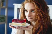 sad woman staring at candle on slice of cake illustrating that she hates her birthday