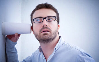 nosy man holding cup against a wall