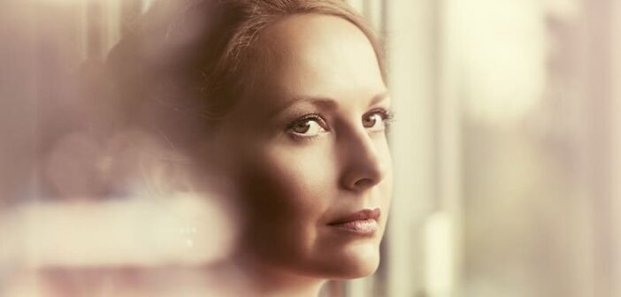 shy woman looking out of window illustrating the need to be more open toward people