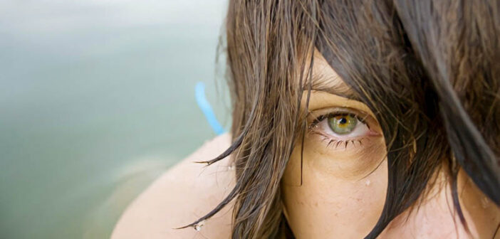 closeup of woman's face as she emerges from water
