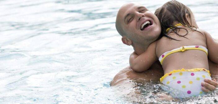 a dad playing with his daughter in a swimming pool