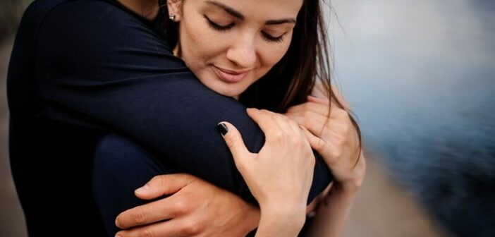 man hugging his girlfriend from behind illustrating her need for constant reassurance in their relationship