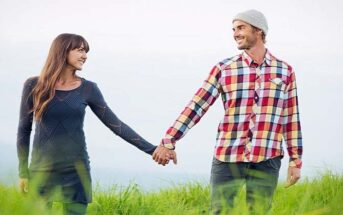 couple holding hands walking through grassy field illustrating patience in a relationship