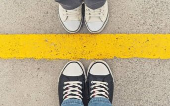 feet of people standing on the opposite side of a yellow line illustrating respecting each other's boundaries